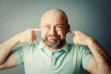 a bearded middle-aged man covers his ears, does not want to hear