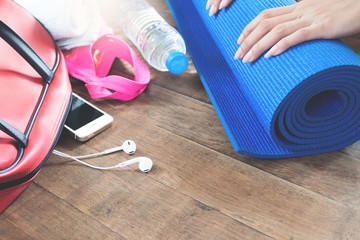 Equipment and accessories with mobile phone for woman workout on wood floor. Copy space