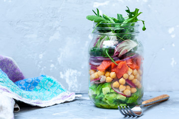 Green salad with layers of salmon, avocado and chickpeas in the jar. Love for a healthy food concept