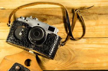 Old soviet rangefinder camera in leather case ona wooden table