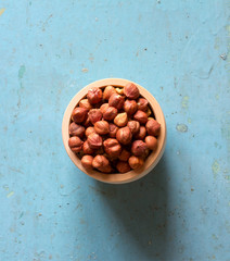 nuts hazelnuts without shell in wooden saucer on the old blue background, top view