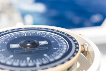 Compass aboard large ship on a blue summer sea.
