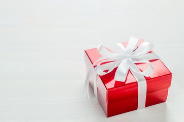 Close up of red gift box with white ribbon bow on white backgrou