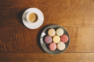 Fresh morning espresso coffee and some french macarons dessert on the wooden table background