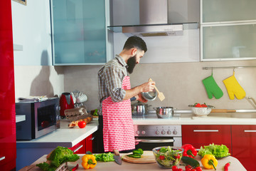awesome bearded man cooking at kitchen making healthy vegetable