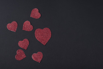 Glittered red Valentine's hearts card on black background