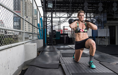 Woman training with kettle bells at rooftop gym in Bangkok