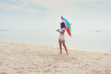 Asian young woman holding rainbow umbrella on the beach , looking for something