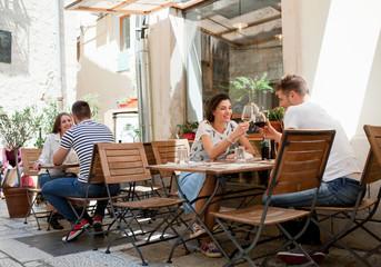 Young couples raising a wine toast at sidewalk restaurant, Split, Dalmatia, Croatia