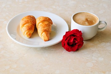 Cup of coffee, croissants and rose on table, romantic breakfast, Valentine Concept