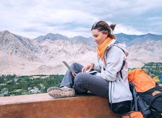 Backpacker with laptop sits on the top view point under mountain