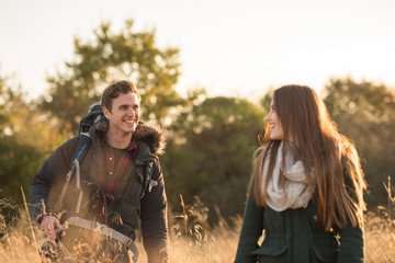Young couple walking through field