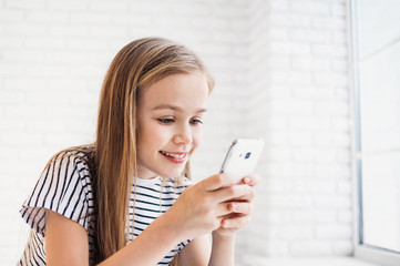 Cute little girl using smart phone at home