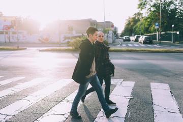 Young lesbian couple walking across pelican crossing city street