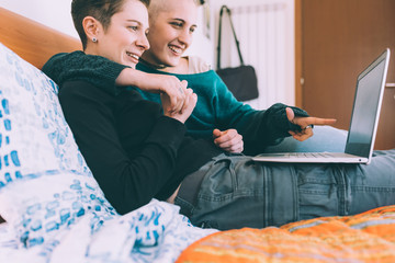 Young lesbian couple reclining on bed pointing at laptop
