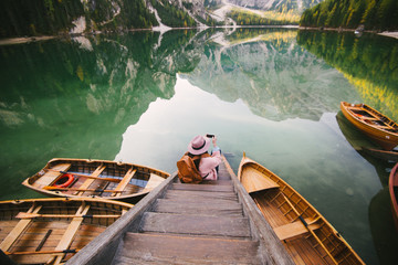 Woman relaxing on pier, Lago di Braies, Dolomite Alps, Val di Braies, South Tyrol, Italy