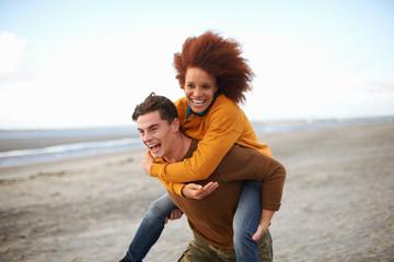 Couple playing piggyback on beach