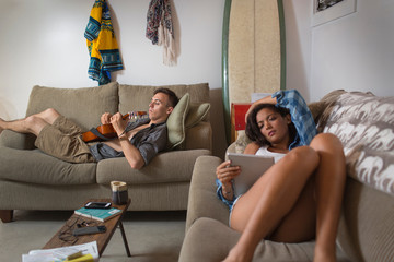 Young couple relaxing on sofa using digital tablet and playing guitar