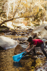 Young hiker fishing with plastic bag in river, California, USA