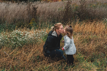 Mid adult woman kissing toddler daughter in field of long grass
