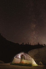 Hiker in tent at night, California, USA
