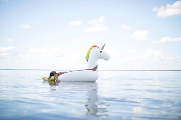 Young man lying back on inflatable unicorn in sea, Santa Rosa Beach, Florida, USA