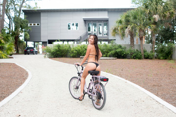 Portrait of young woman in bikini looking back from bicycle on driveway, Santa Rosa Beach, Florida, USA