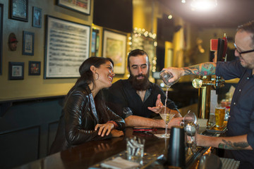 Bartender pouring cocktail for young couple in public house