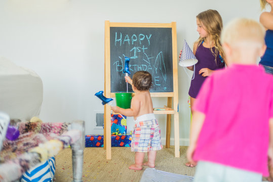Toddler playing with balloon at blackboard at birthday party