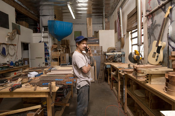Guitar maker in workshop making telephone call on mobile phone