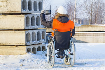 Disabled worker on wheelchair take photos on tablet in construction site