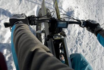 ebike - mountain bike elettrica - fat bike da neve, che sale in alta montagna con gli sci caricati sulla bici, Riale, Val Formazza, Ossola, Alpi Italia