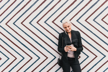 Woman in front of zig zag pattern wall using smartphone