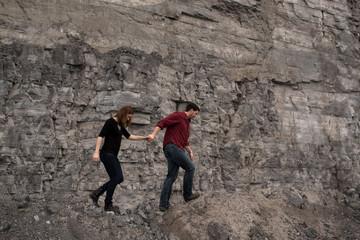 Couple walking on side of cliff, Ottawa, Ontario