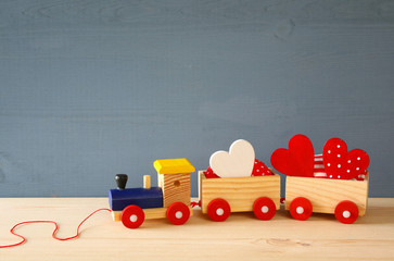 Wooden toy train with herts on the table
