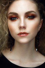 Beautiful woman portrait on black background with colorful make up in orange colors.