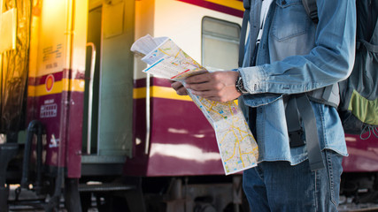 Young traveler standing beside a train alone with travel map on