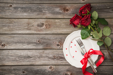 romantic table setting with a white dish and red roses