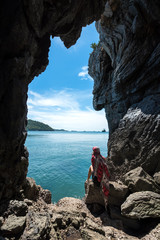 Travel young women in a cave near the sea in Keo Sichang, Thailand.