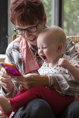 Grandmother holding a toddler and looking at a cellphone