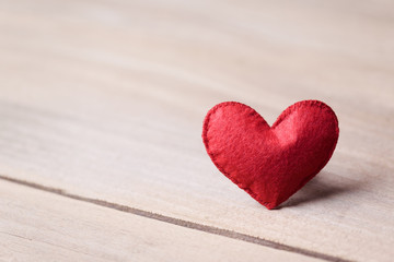 Valentines day concept of one heart shape decoration with old wood floor background.