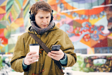 Man listening to music with headphones looking to the phone and drinking coffee in the winter on the street. Concept of technology and lifestyle
