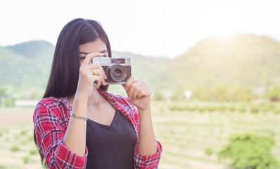 Young hipster woman photographer holding a vintage camera.