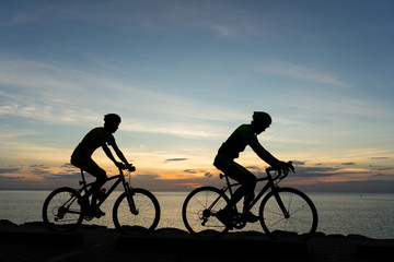 Foto op Aluminium Fietsen Silhouettes of Cyclists on bicycle at the ocean in the sunset sc