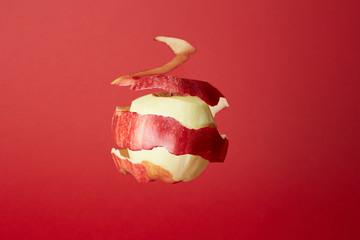Mela rossa sospesa sbucciata su fondo rosso