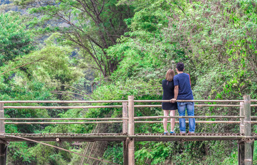 Man and Woman taking photos on the wooden bridge.