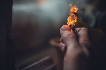 A man's hand holding a lighter with a flame.
