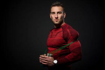 Muscular man skipping rope. Portrait of muscular young man exercising with jumping rope on black background.