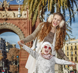 cheerful modern mother and child in Barcelona, Spain