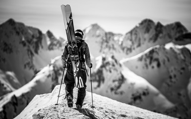 A skier hiking up the side of a mountain.